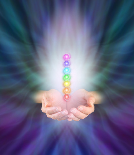 Healer's hands emerging from feather like multicolored energy formation background, cupped with seven chakra vortexes hovering above in a misty light with plenty of copy space