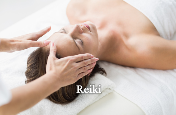 Cropped hands of therapist performing reiki on woman at spa